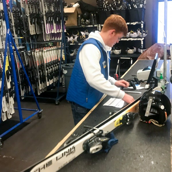 Rental shop employee adjusting skis
